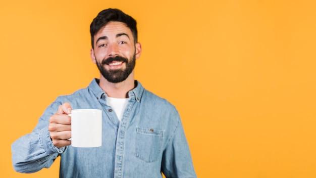 Вид спереди парень держит чашку