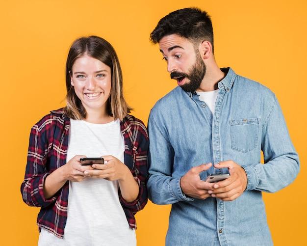 自分の携帯電話と正面のカップル