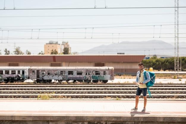 ロングショット笑みを浮かべて男が電車を待っています。
