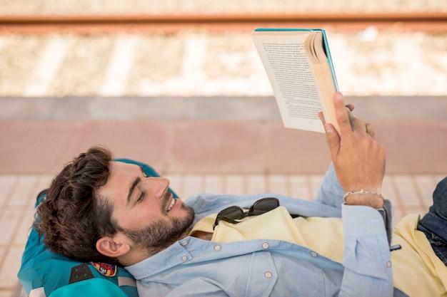 横に男が電車の駅で本を読んで