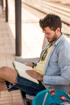 Боком мужчина читает книгу на вокзале