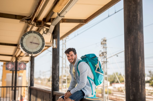 電車を待っている笑顔の旅行者