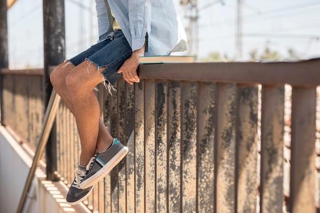 電車を待っているフェンスの上に座っている男