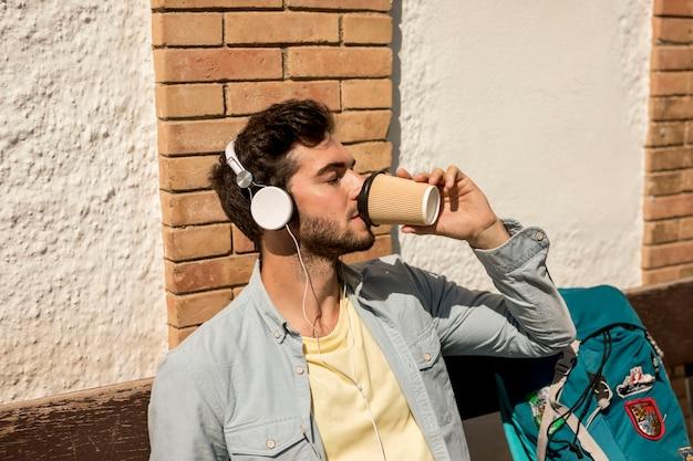 ミディアムショットトラベラーがコーヒーを飲む