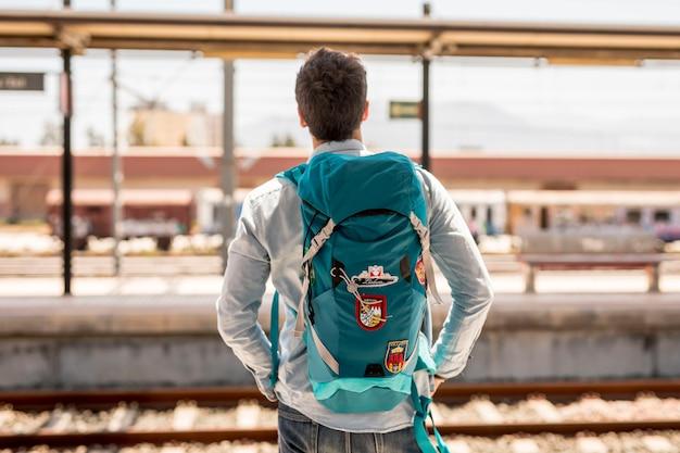 電車を待っている旅行者の背面図
