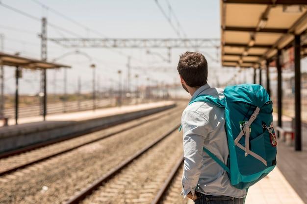電車を探している横向きの旅行者
