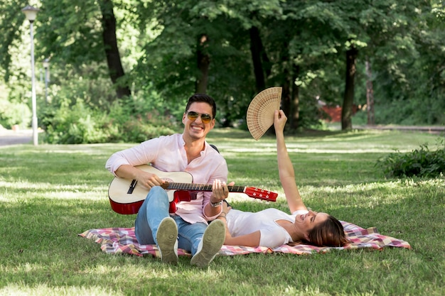 スマイリー男が公園でギターを弾く