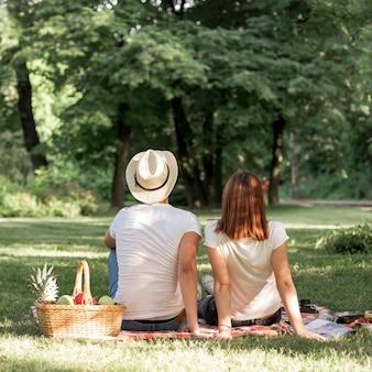 ピクニックで毛布の上に座っている背面図カップル