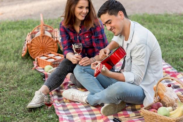 若い男が彼のガールフレンドのためにギターを弾く