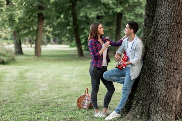 彼のガールフレンドのためにギターを弾く男