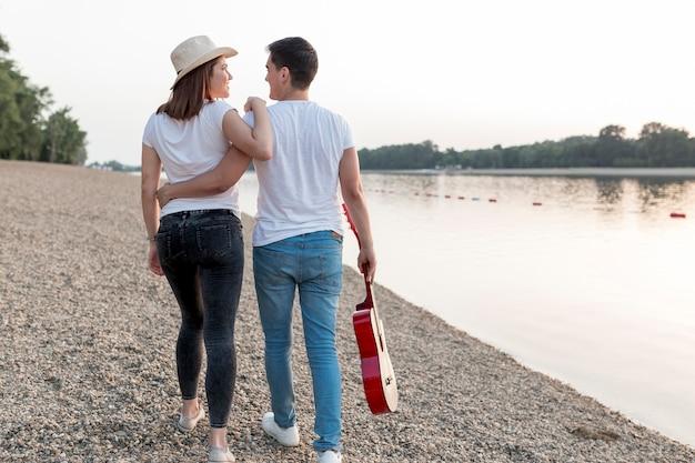 若いカップルがビーチを歩いてギターを運ぶ