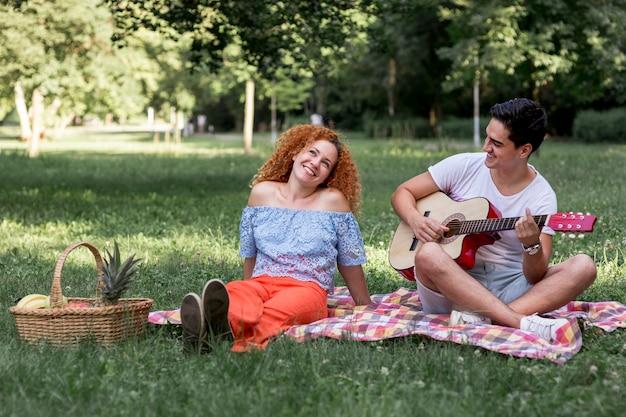 赤い髪の女性と彼女のボーイフレンドは毛布の上に座って