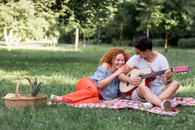 公園で遊び心のあるカップルのロングショット