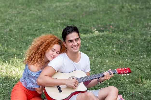 公園で彼女のボーイフレンドを抱き締める女性のハイアングル