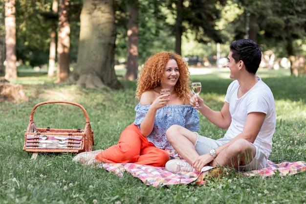 幸せなカップルが公園で毛布でリラックス