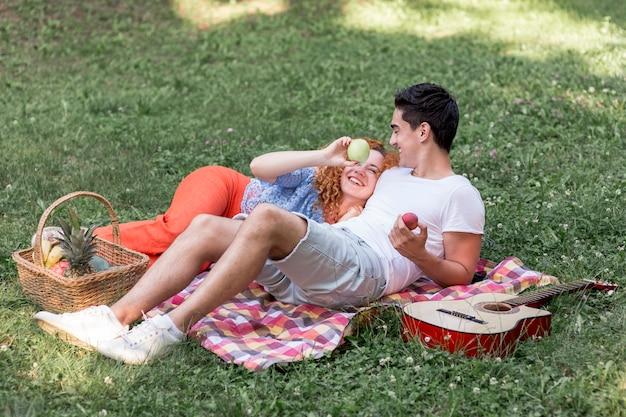 かわいいカップルが公園で毛布で休む
