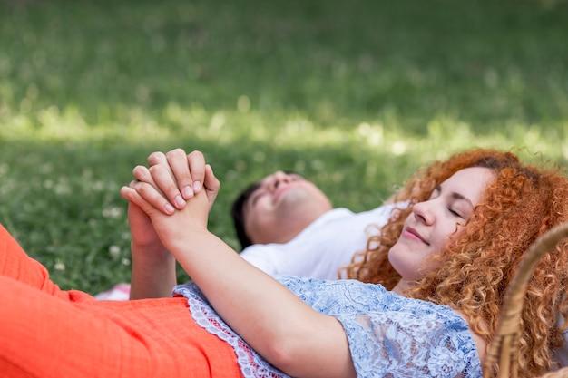 座っていると手を繋いでいるカップルのクローズアップ