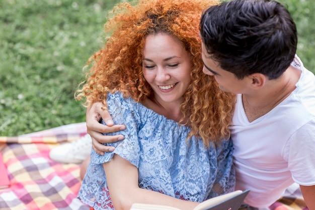 幸せな笑顔若いカップルが公園で寄り添う