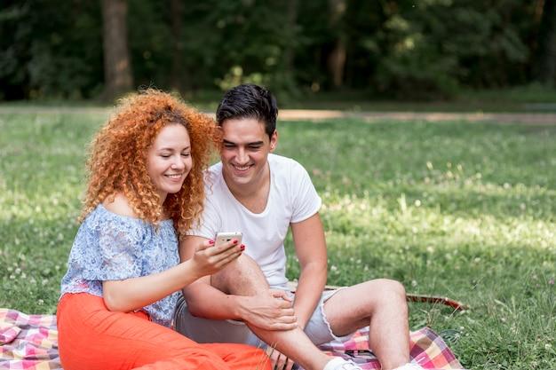幸せなカップルはリラックスして公園で携帯電話をチェック