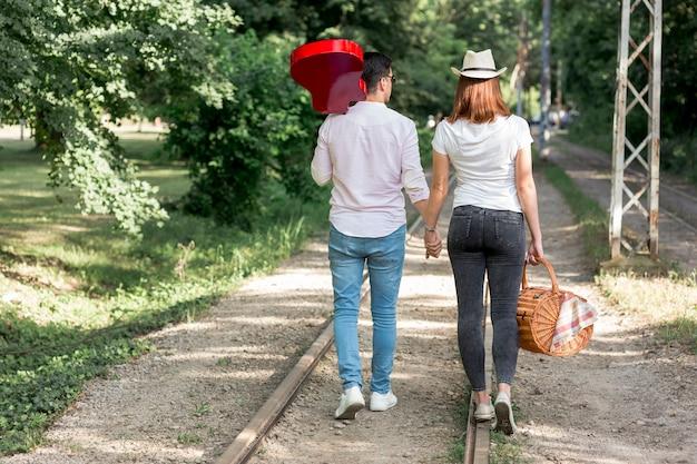 電車の線路に沿って歩くカップル