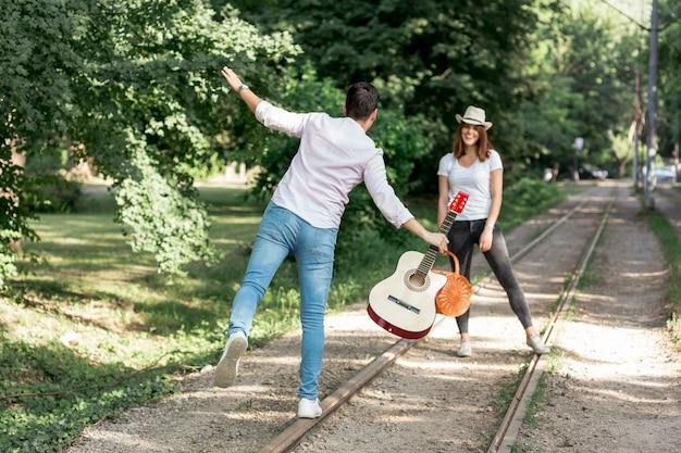 遊び心のあるカップルが鉄道の上を歩く