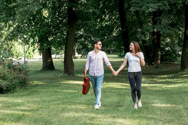 手をつないで草原を歩くロングショットの若いカップル