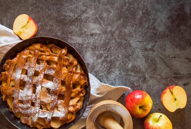 フルーツと木製のテーブルの上の焼きたてのアップルパイ