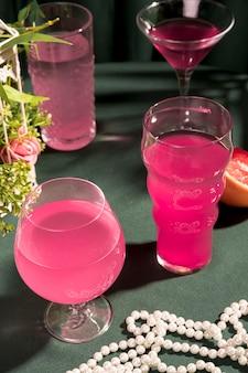 テーブルの上の真珠の横にあるピンクのマティーニ