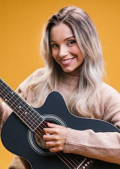 Счастливая привлекательная женщина играет на гитаре на желтом фоне