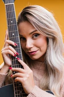 Портрет улыбающейся молодой женщины с гитарой