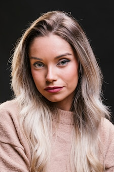 カメラ目線の黒い背景に対して美しい若い女性の肖像画