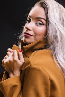 黄色のジャケットを押しながら黒の背景にポーズをとって若い女性のクローズアップ