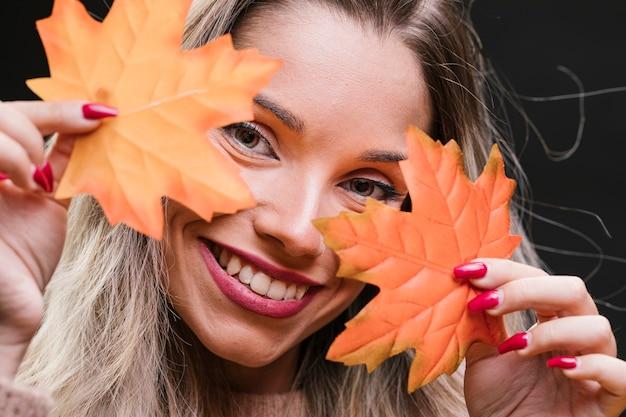 カエデの葉を保持している若い美しい女性のクローズアップ