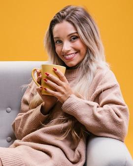 カメラ目線のコーヒーのカップを保持しているソファーに座っていた美しい女性