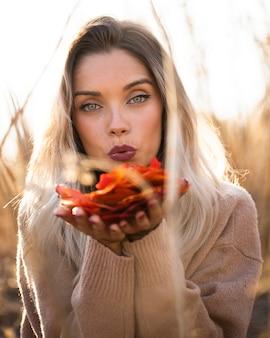 魅力的な若い女性は屋外でカメラを見て紅葉を吹いて