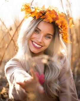 メープルを着て笑顔の女性の肖像画は屋外で花輪を残します