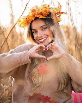 メープルを着て魅力的な若い女性の手でハートの形を作るティアラを葉します。
