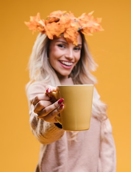 コーヒーカップを保持している葉の花輪を身に着けている陽気な若い女性
