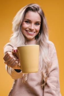 一杯のコーヒーを与えるとカメラ目線の美しい若い女性
