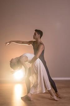 フルショットのカップルが一緒に踊る