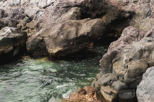 岩が多い海岸に触れるクローズアップ海