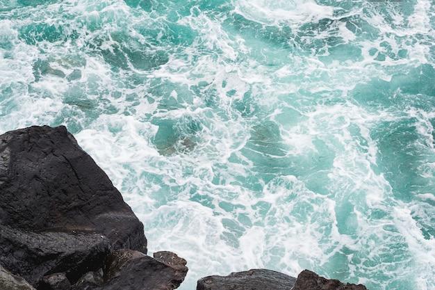 Макро волнистая вода на скалистом берегу
