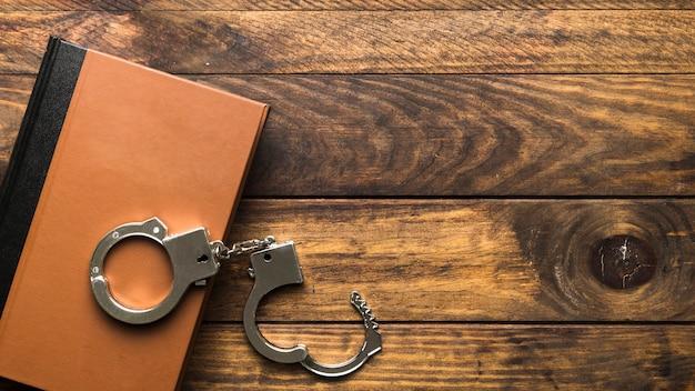 トップビュー本と木製のテーブルの上の手錠