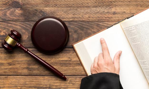 開いた本と小槌を持つ平らな裁判官