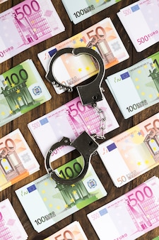 Плоские лежал банкноты на деревянный стол с наручниками