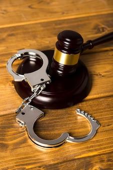 Крупный план с молотком судьи на деревянной подставке с наручниками