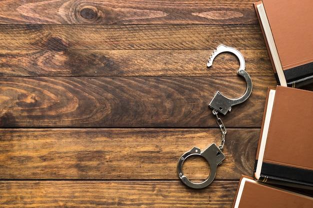 Плоская лежащая рамка с книгами и наручниками