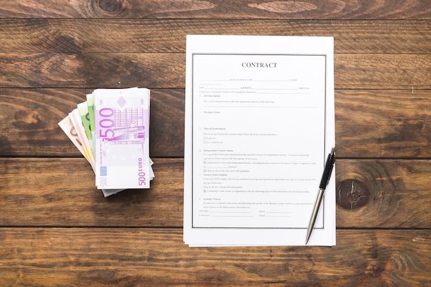木製のテーブルにお金とフラットレイアウト契約