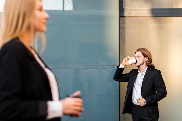 ビジネスの男性が外でコーヒーを飲む