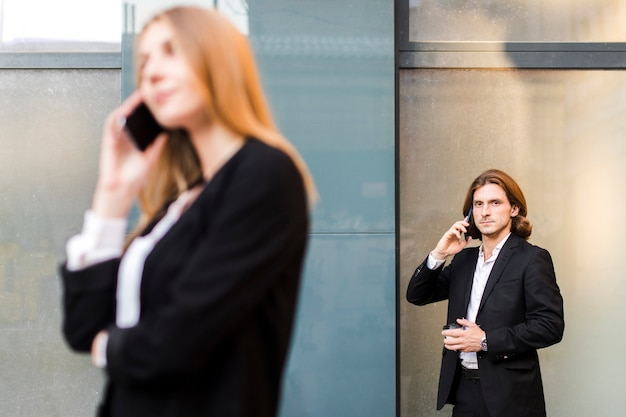 Мужчина разговаривает по телефону с женщиной не в фокусе